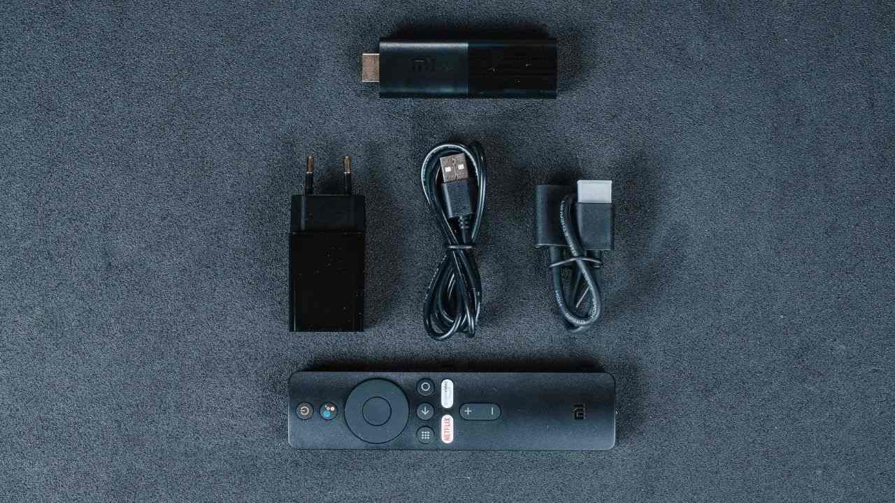 Mi TV Stick e seus acessórios, como controle remoto e cabos, em um fundo cinza