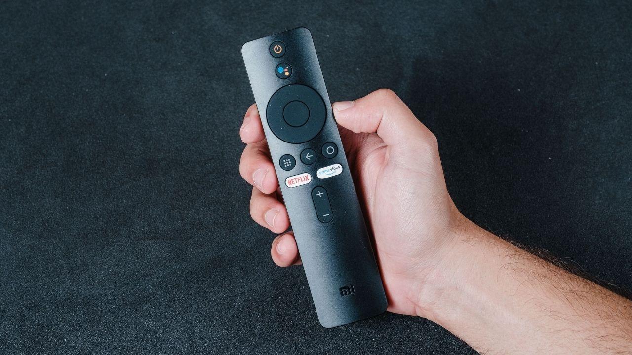 Mão masculina segurando o controle remoto da Mi TV Stick em um fundo cinza