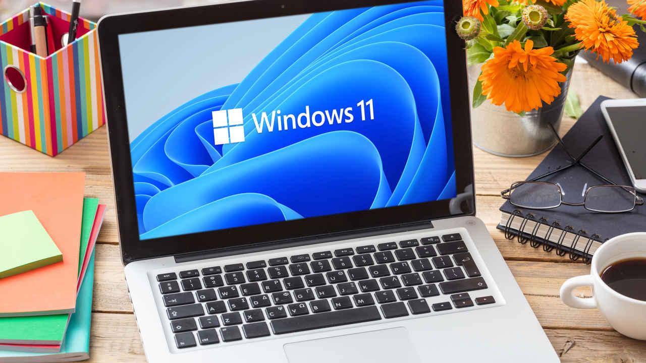 Notebook em uma mesa com fundo de tela da Microsoft