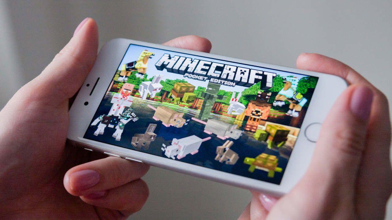 Pessoa segurando celular com Mods para Minecraft PE
