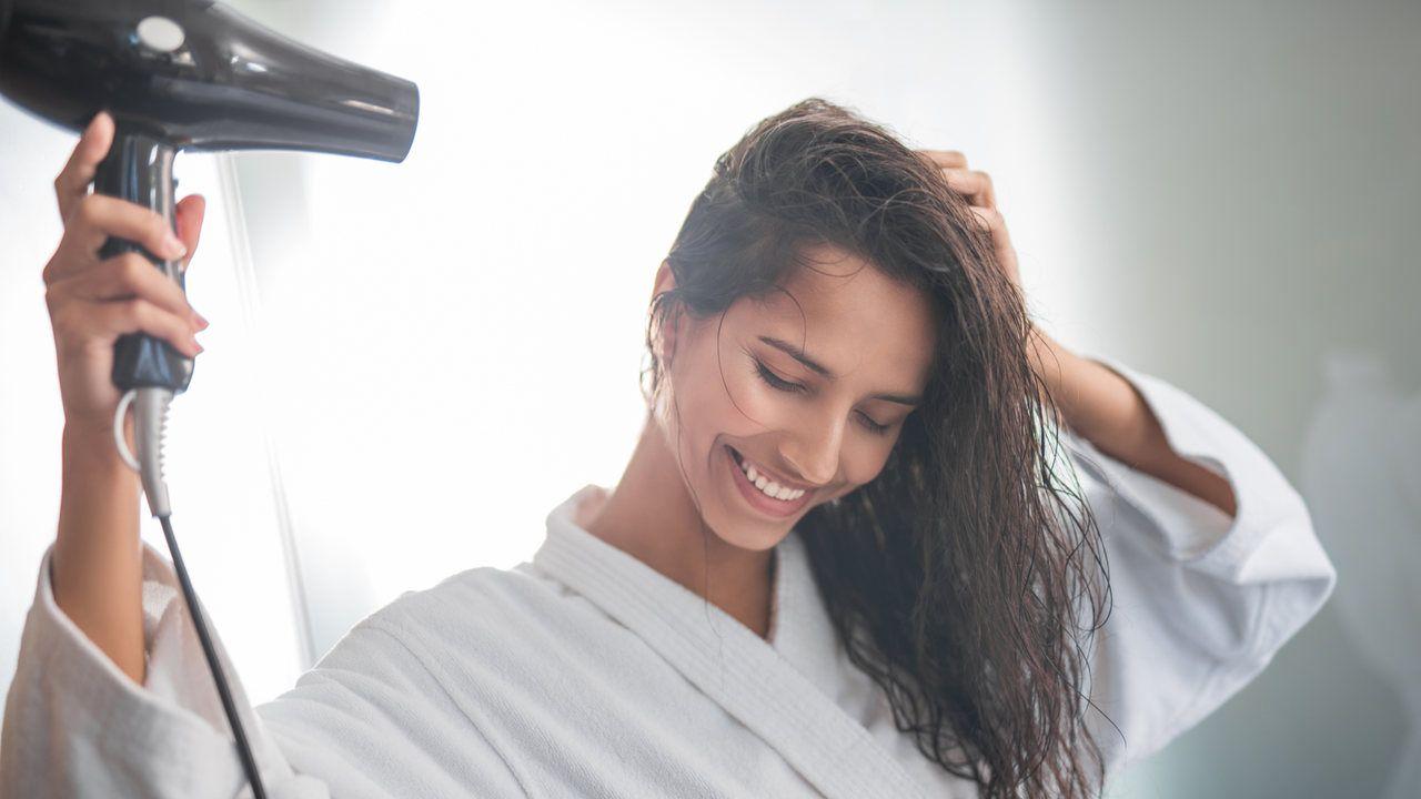 Mulher secando os cabelos antes de fazer cachos com chapinha