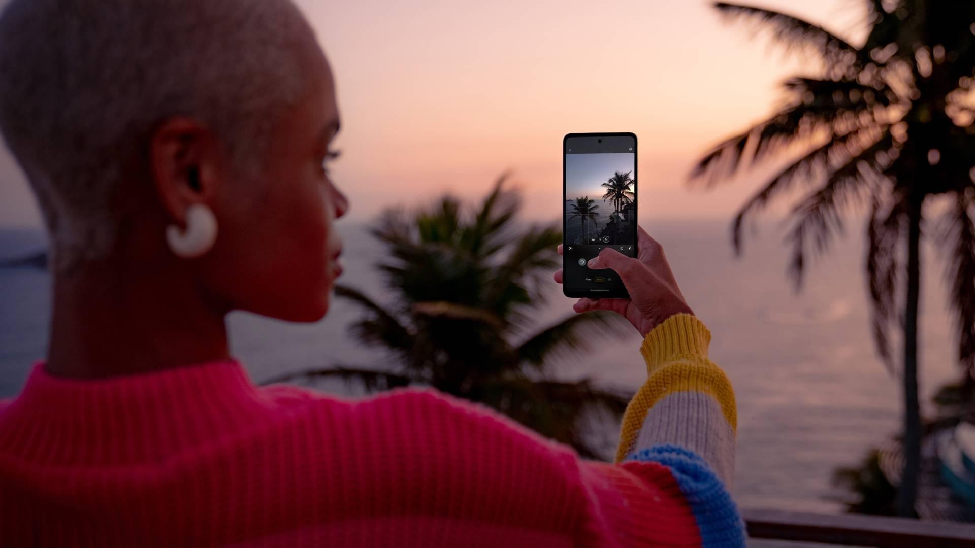Mulher segurando Moto G60s e fotografando uma paisagem com coqueiros
