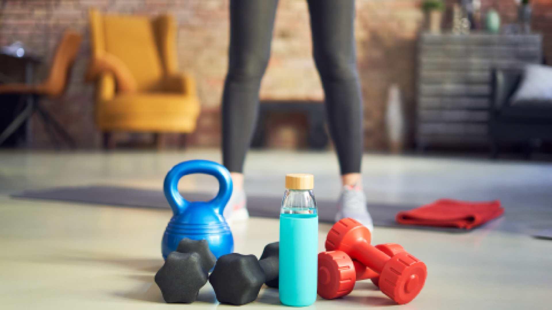 Itens de musculação em casa dispostos numa sala de estar