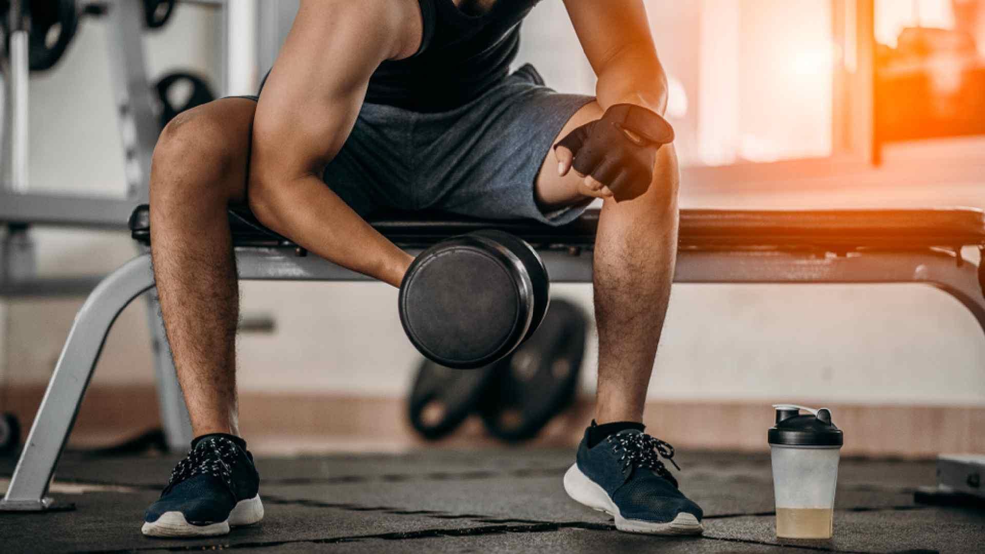 Homem segurando um halter com peso na academia