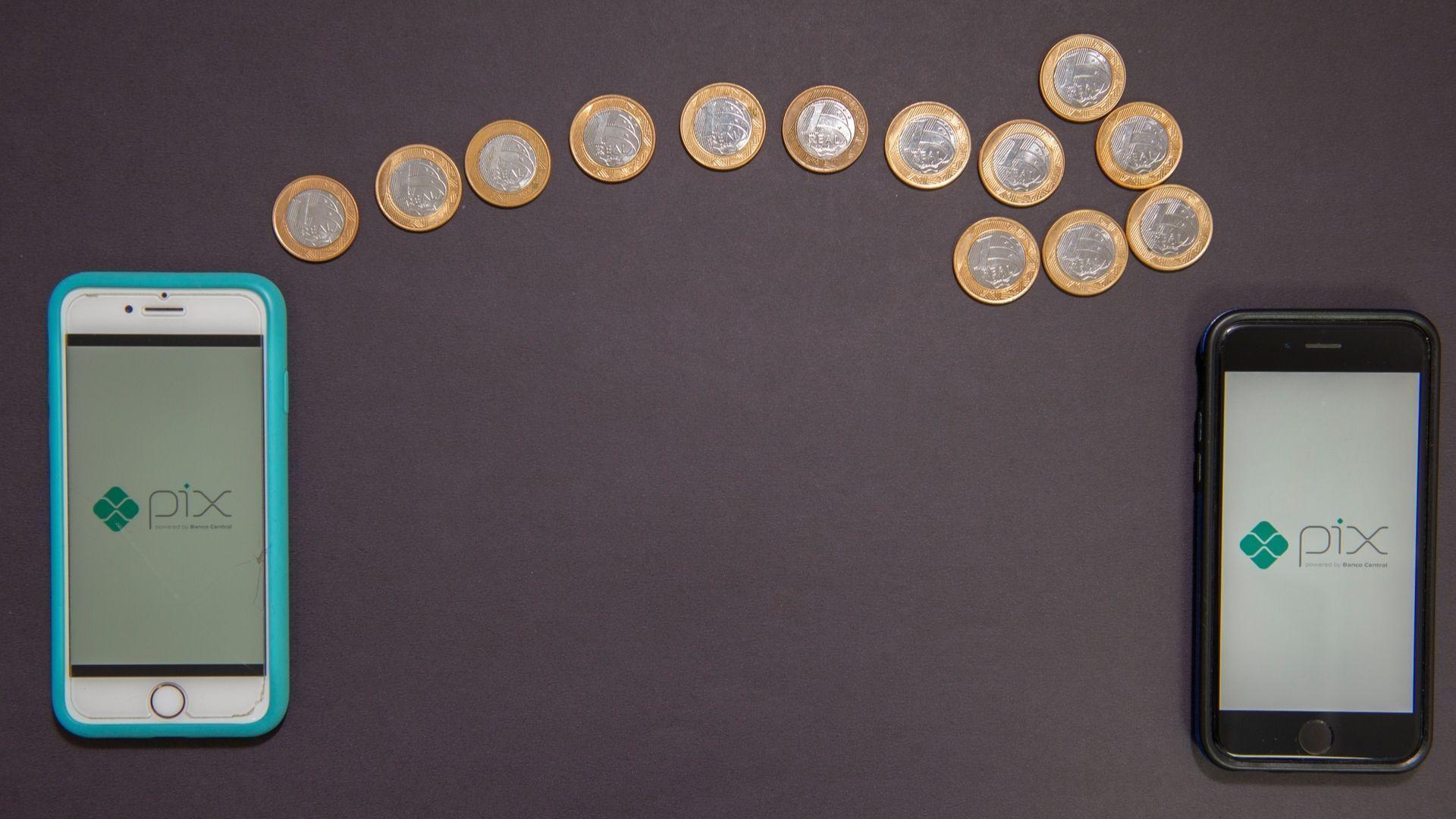 Dois celulares, um em cada canto da imagem, com uma seta feita de moedas de um real ligando um ao outro