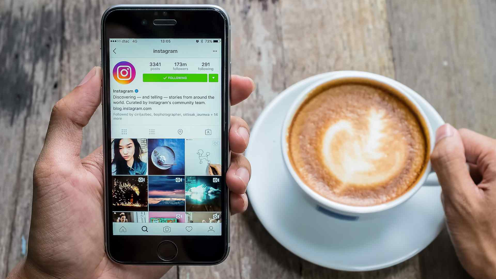 Pessoa lê a biografia para Instagram no celular enquanto toma uma xícara de café