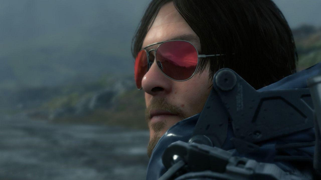 Rosto do personagem Sam de Death Stranding ao ar livre, com óculos escuros refletindo a paisagem