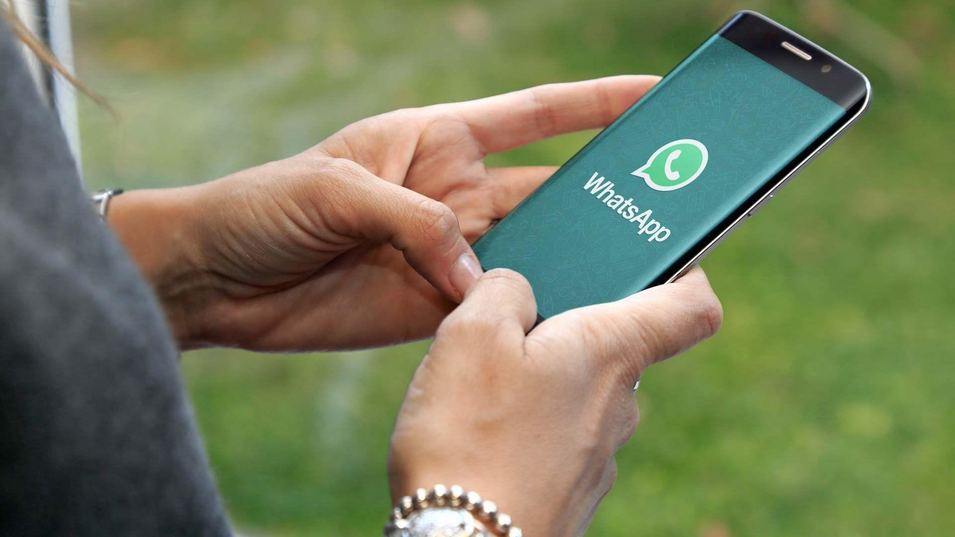Mulher segurando um celular com o símbolo do WhatsApp na tela.