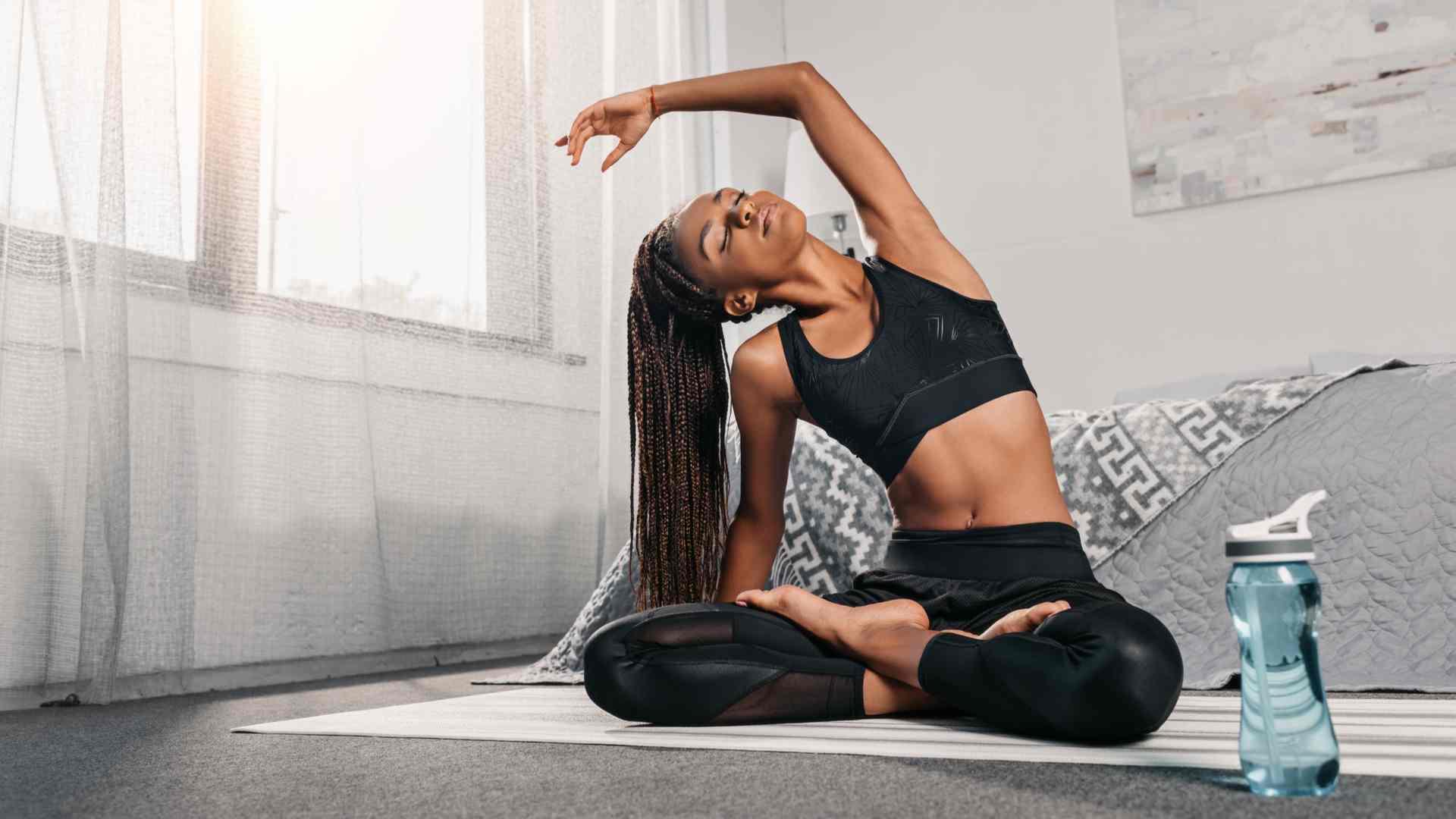 Mulher fazendo yoga dentro do quarto