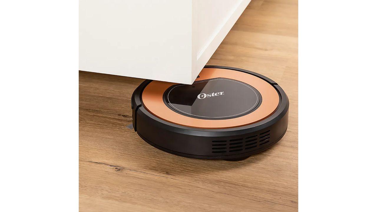 Aspirador robô Oster em chão de madeira, passando debaixo de um móvel branco.