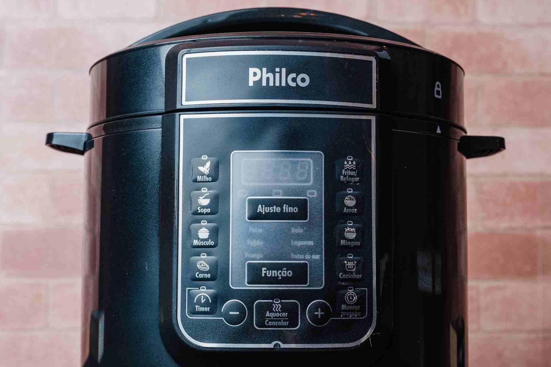 Visão frontal da panela de pressão elétrica Philco na frente de uma parede de tijolinhos