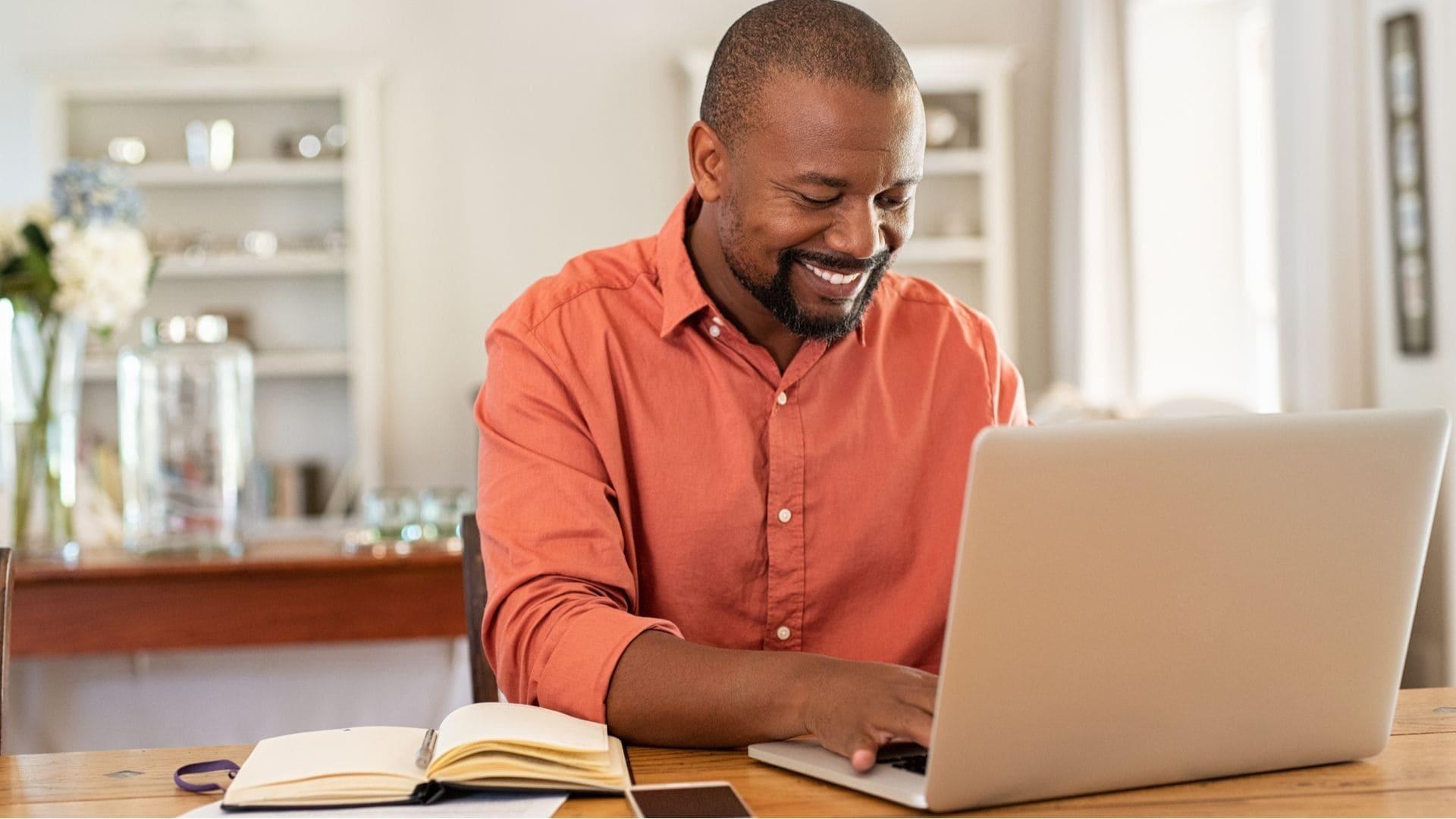 Homem usando computador em mesa de madeira