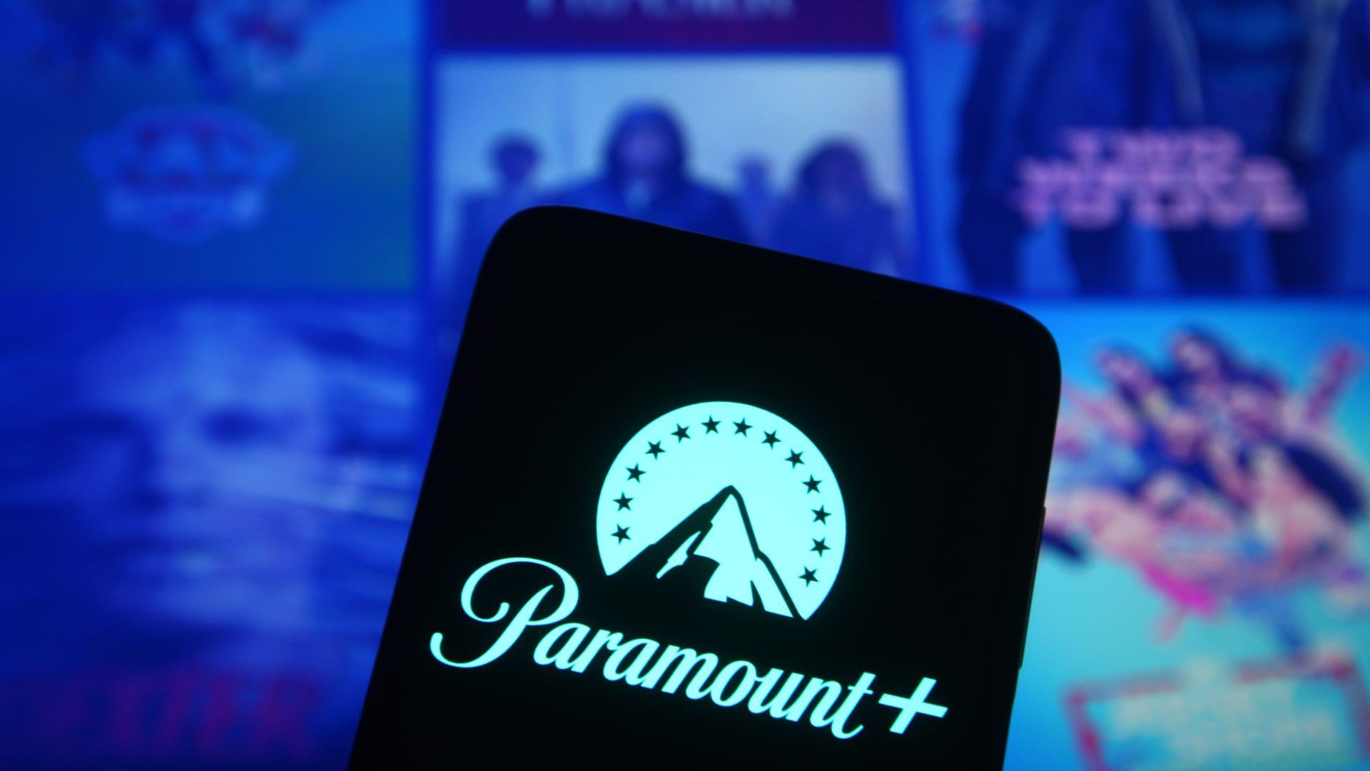 Logomarca do Paramount Plus aberta em um celular, com catálogo do streaming desfocado no fundo.