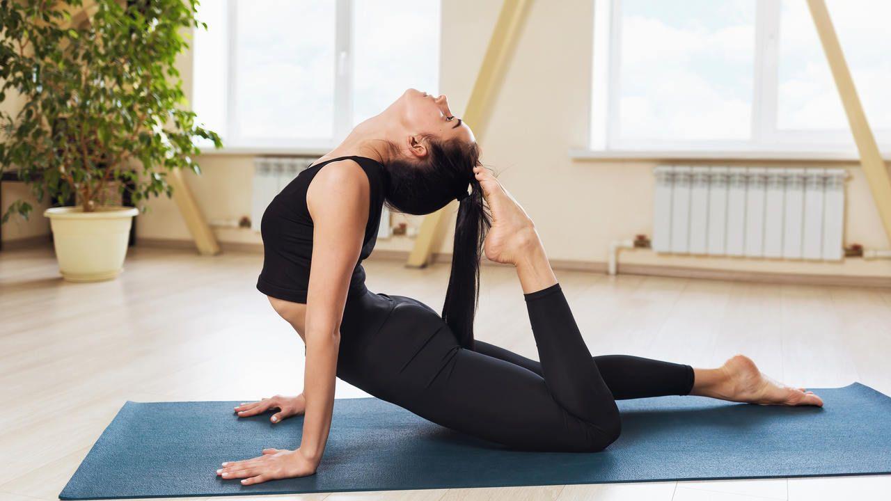 Mulher fazendo pilates em cima de tapete azul