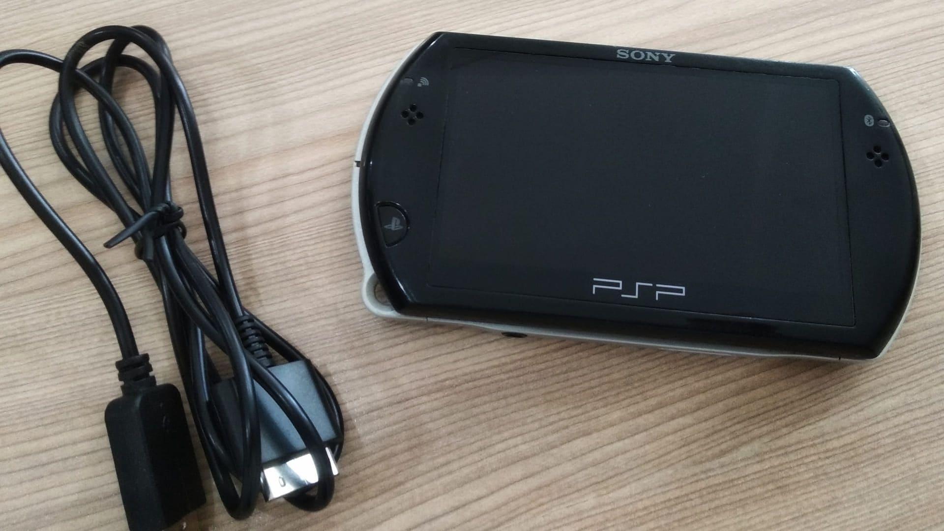 PSP preto e cabo em mesa de madeira