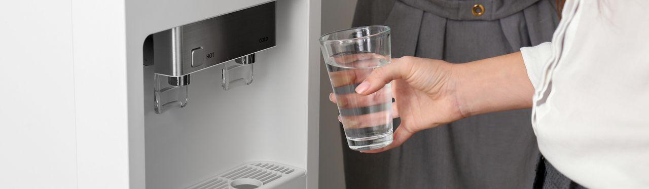 Mão segurando um copo cheio d'água próximo a um purificador.