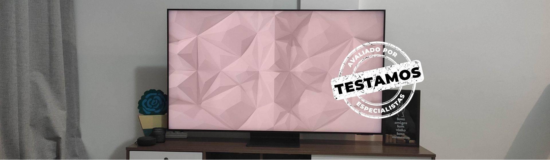Smart TV Samsung QN90A em cima de um rack em Modo Ambiente. A parede ao fundo é branca.