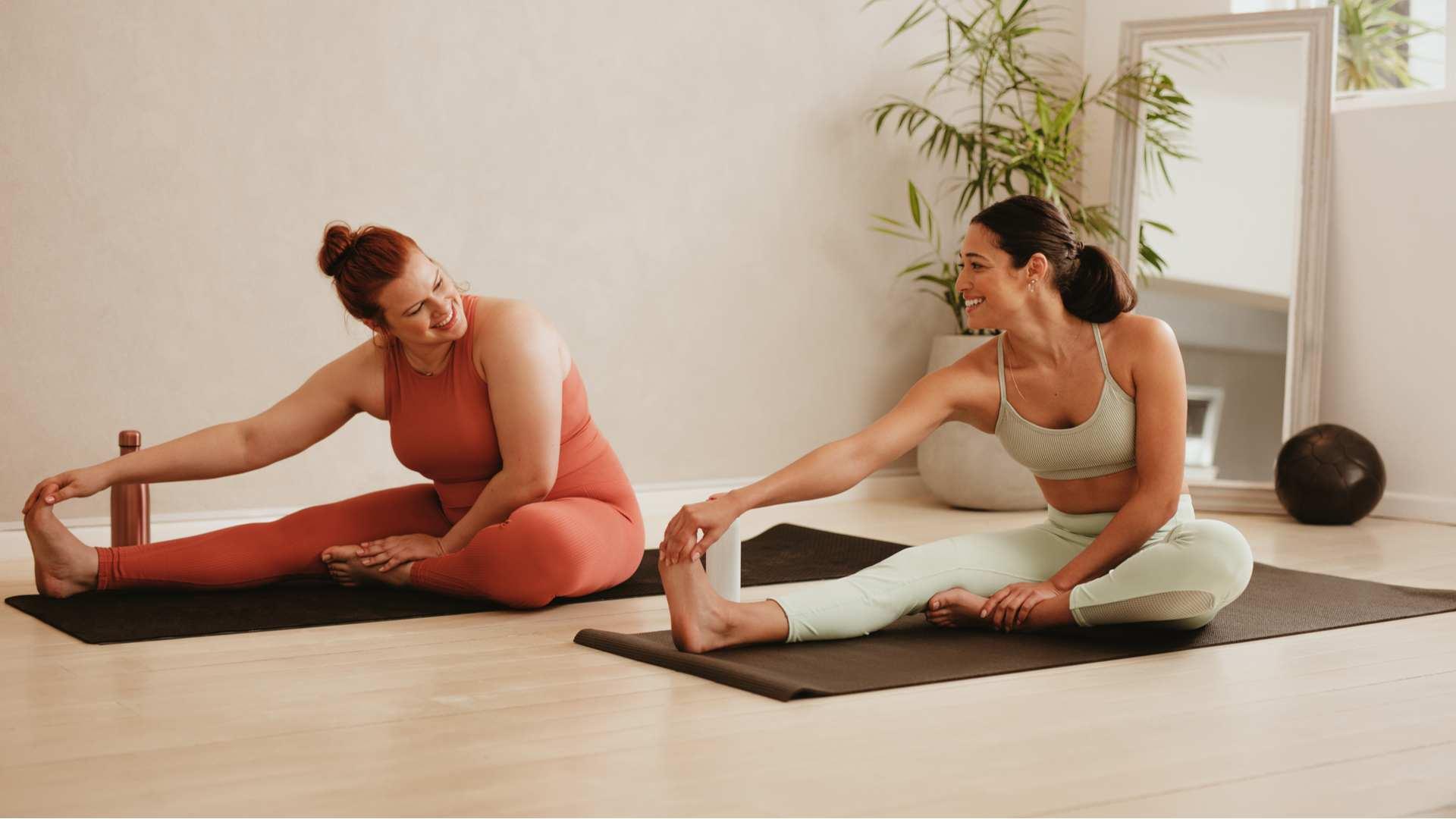 Duas mulheres fazendo yoga em casa