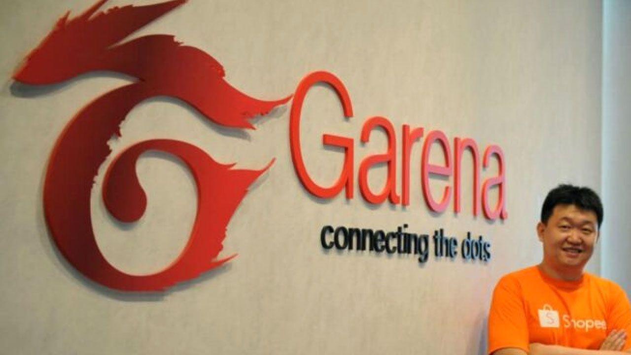 Forrest Li dono da Garena encostado na parede com logo da empresa