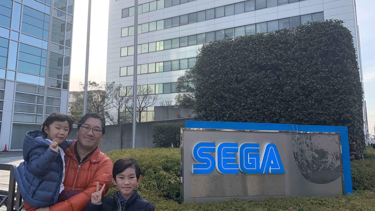 Yuji Naka, criador de Sonic, e seus dois filhos em frente ao prédio que costumava ser o escritório da Sega, com uma placa escrito Sega