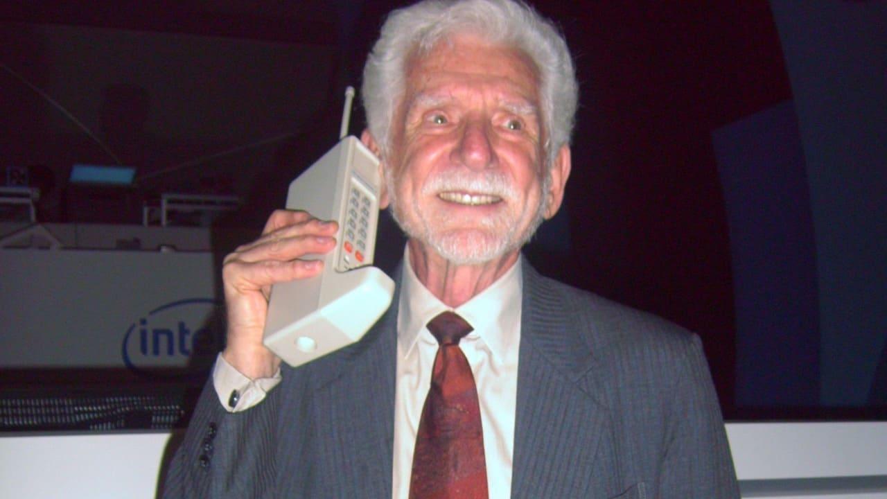 Foto mostra Martin Cooper com celular antigo junto à orelha