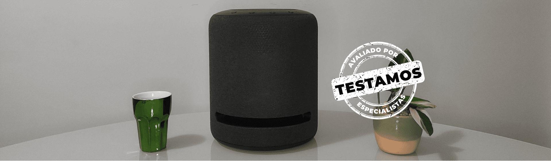 """Amazon Echo Studio apoiado em bancada branca com selo """"Avaliado por Especialistas"""" carimbado na imagem."""