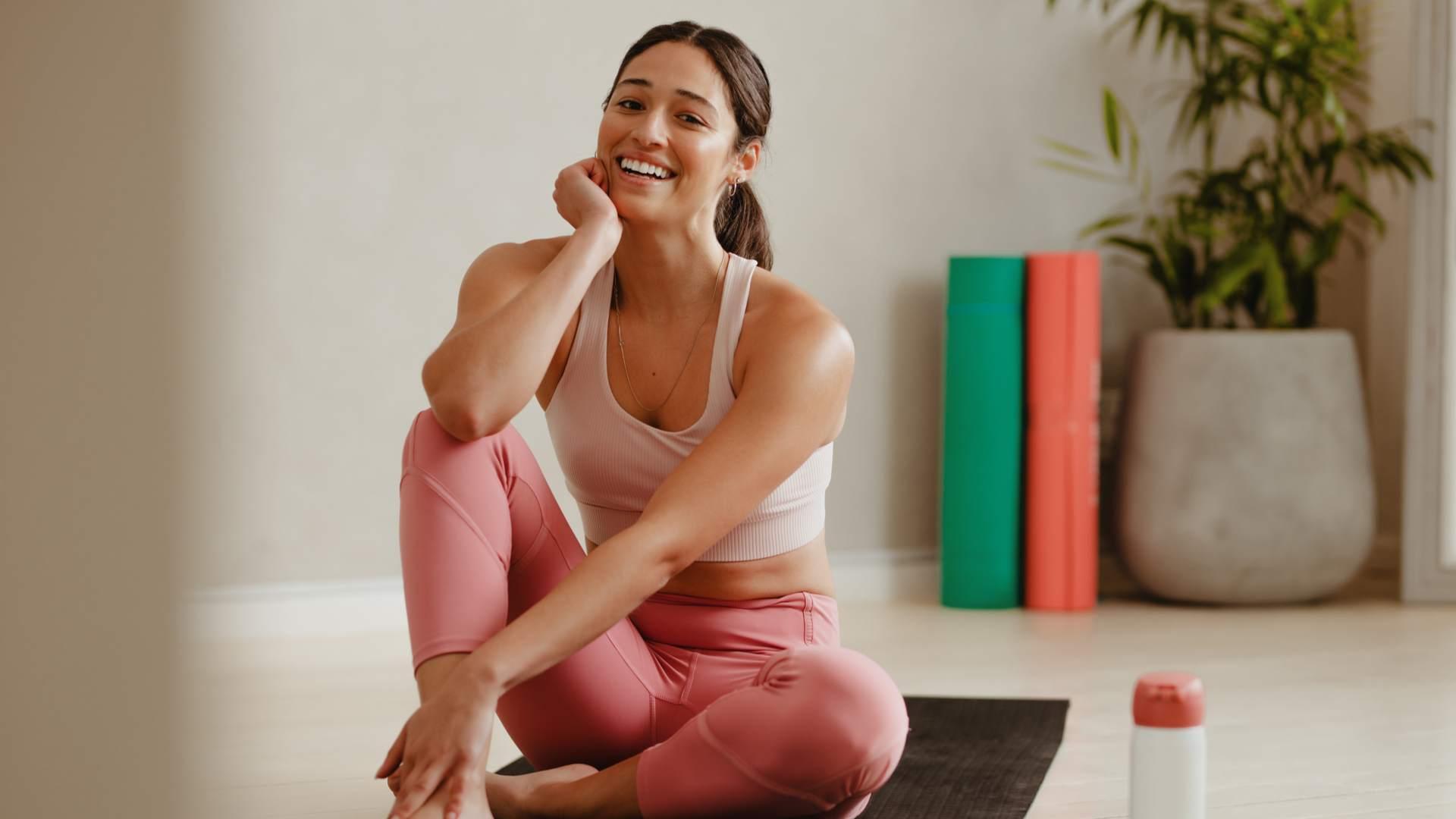 Mulher sentada no tapete de yoga em casa