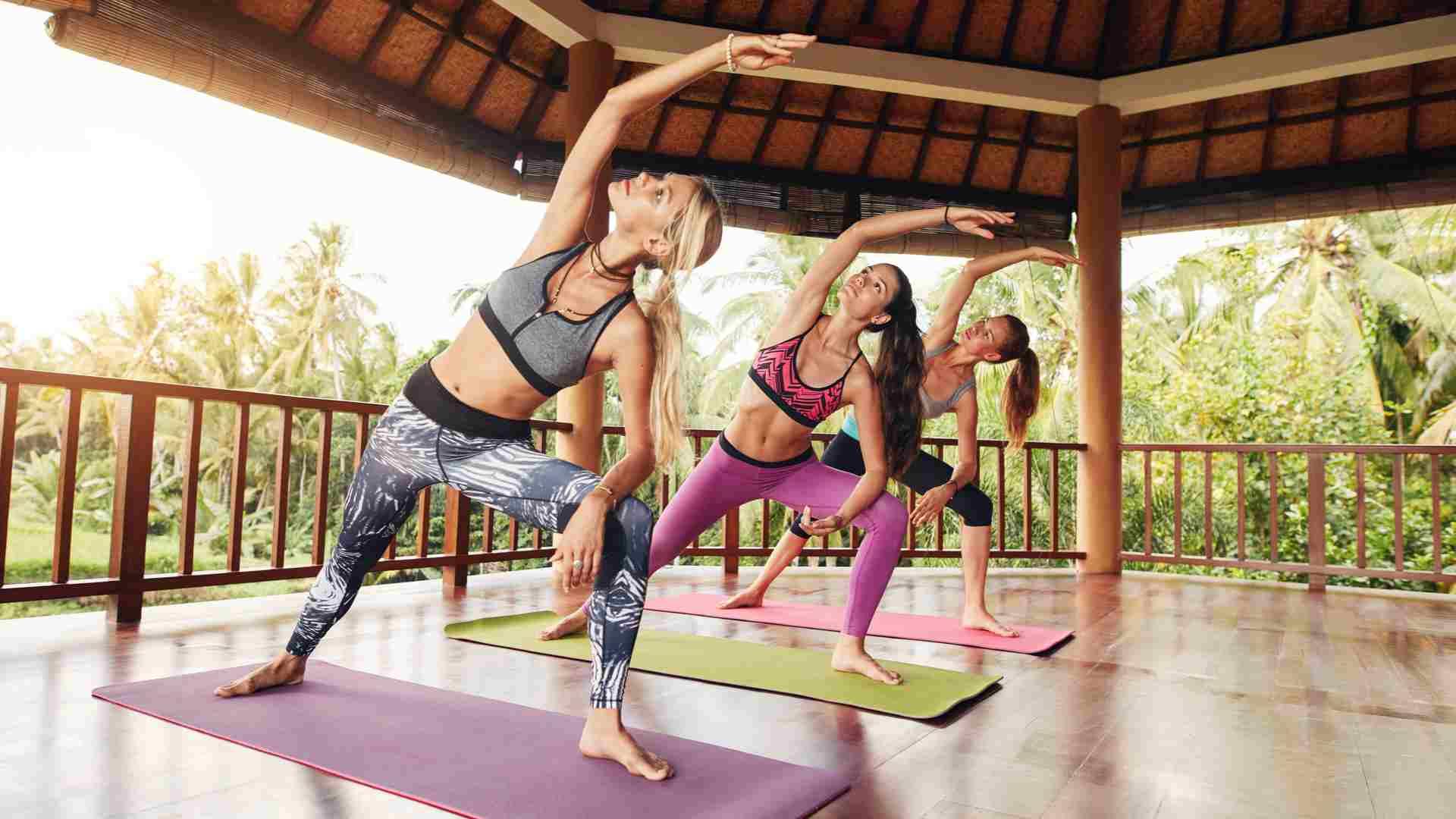 Três mulheres fazendo yoga ao ar livre