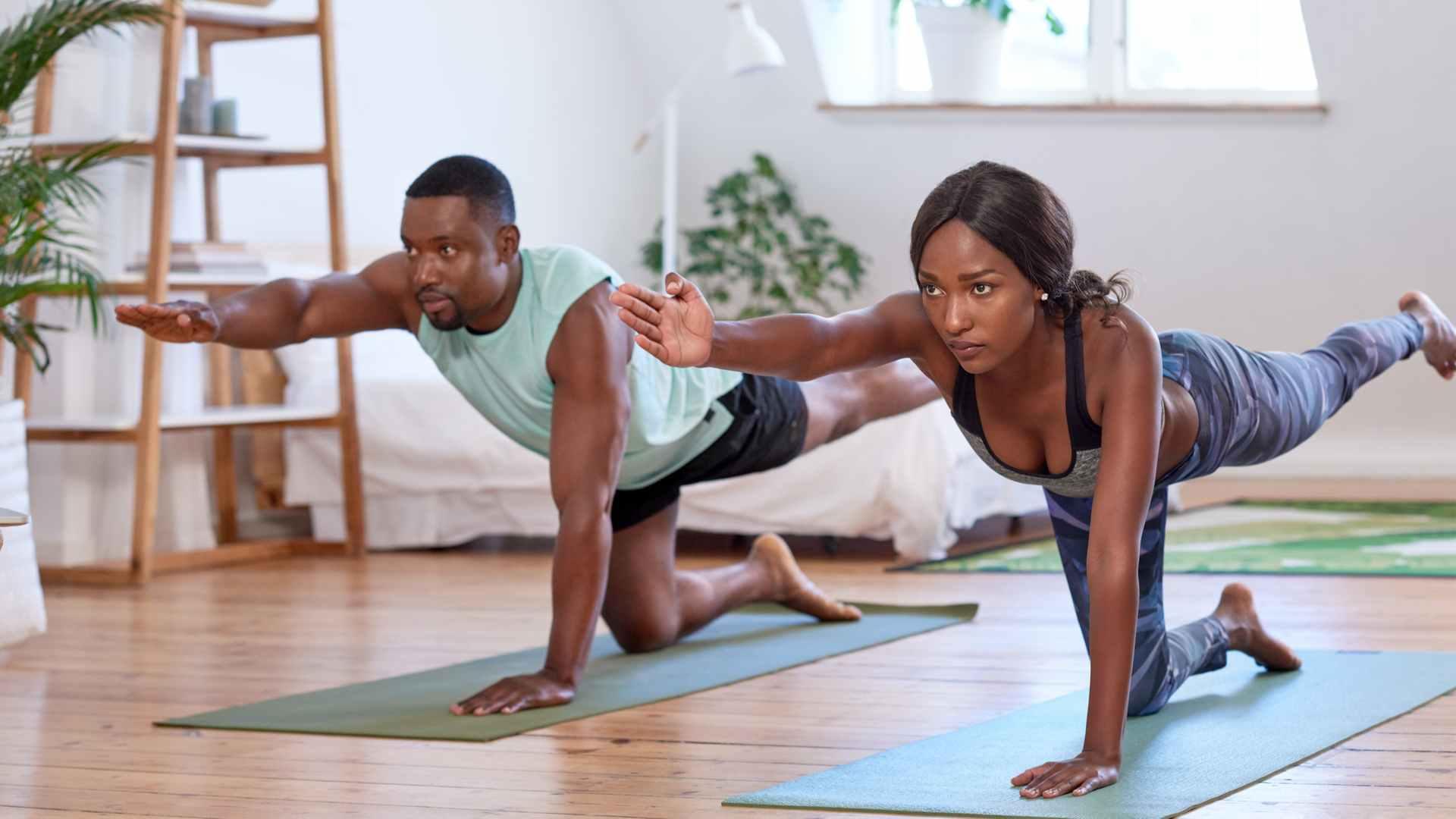 Casal fazendo yoga na sala de casa