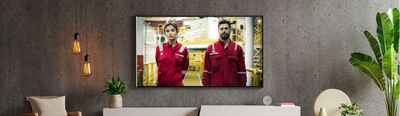 Série Ilha de Ferro, do Globoplay, passando em TV instalada em parede cinza.