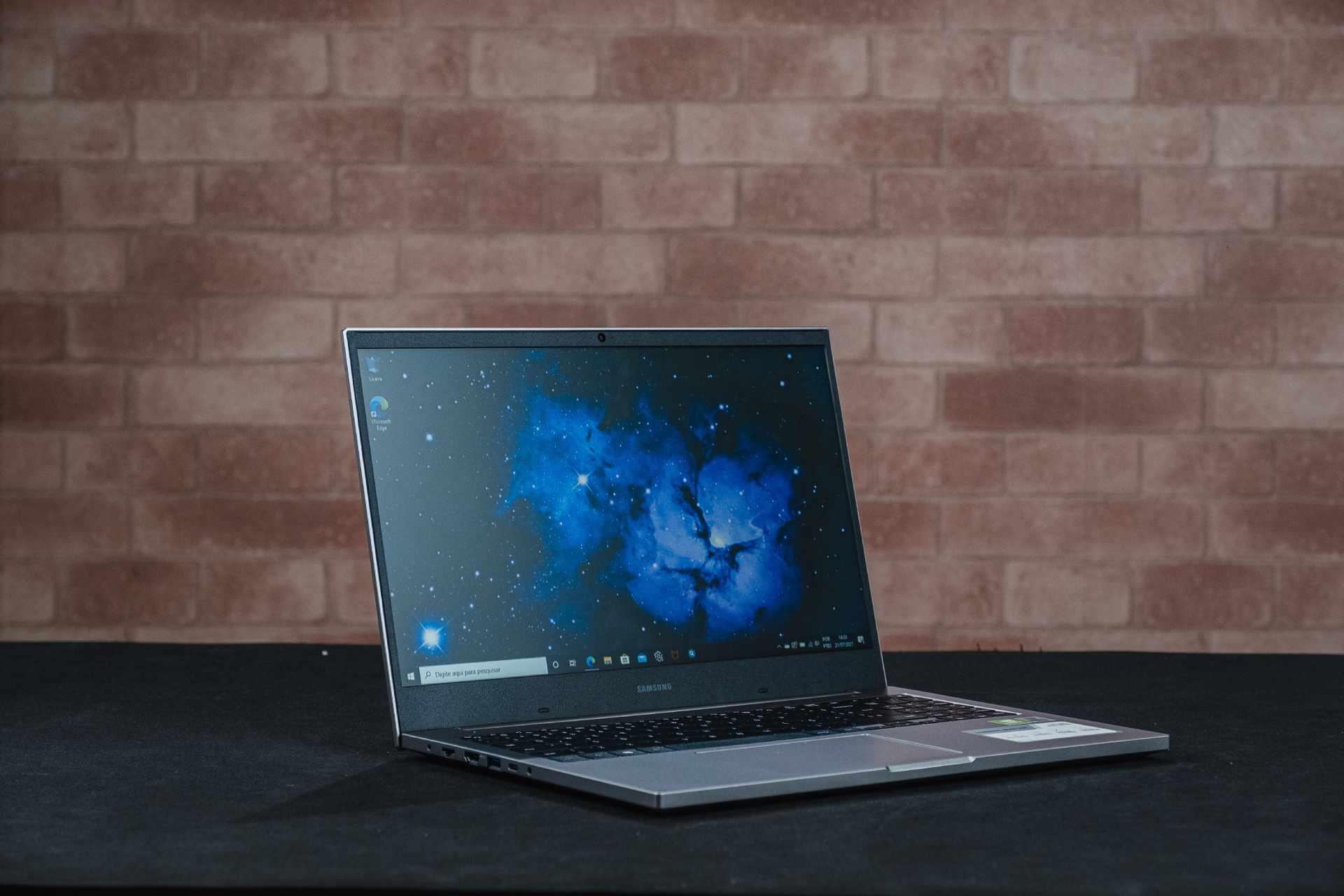Notebook Samsung X50 ligado sobre mesa preta