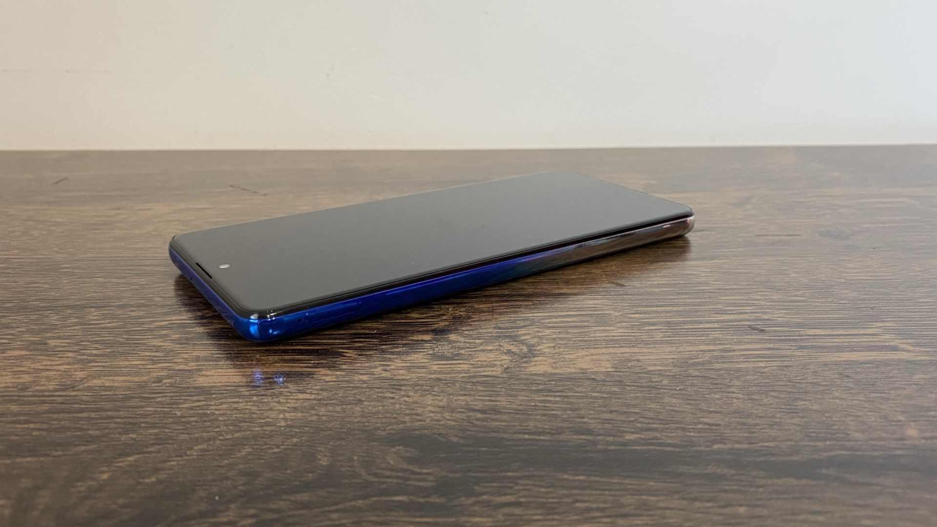 Lateral esquerda do Galaxy M62, enquanto ele está apoiado sobre bancada de madeira.