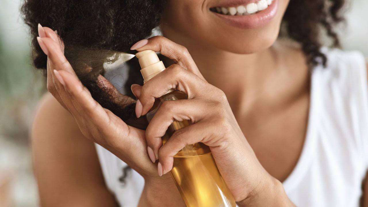 Mulher usando produto dourado em seus cachos