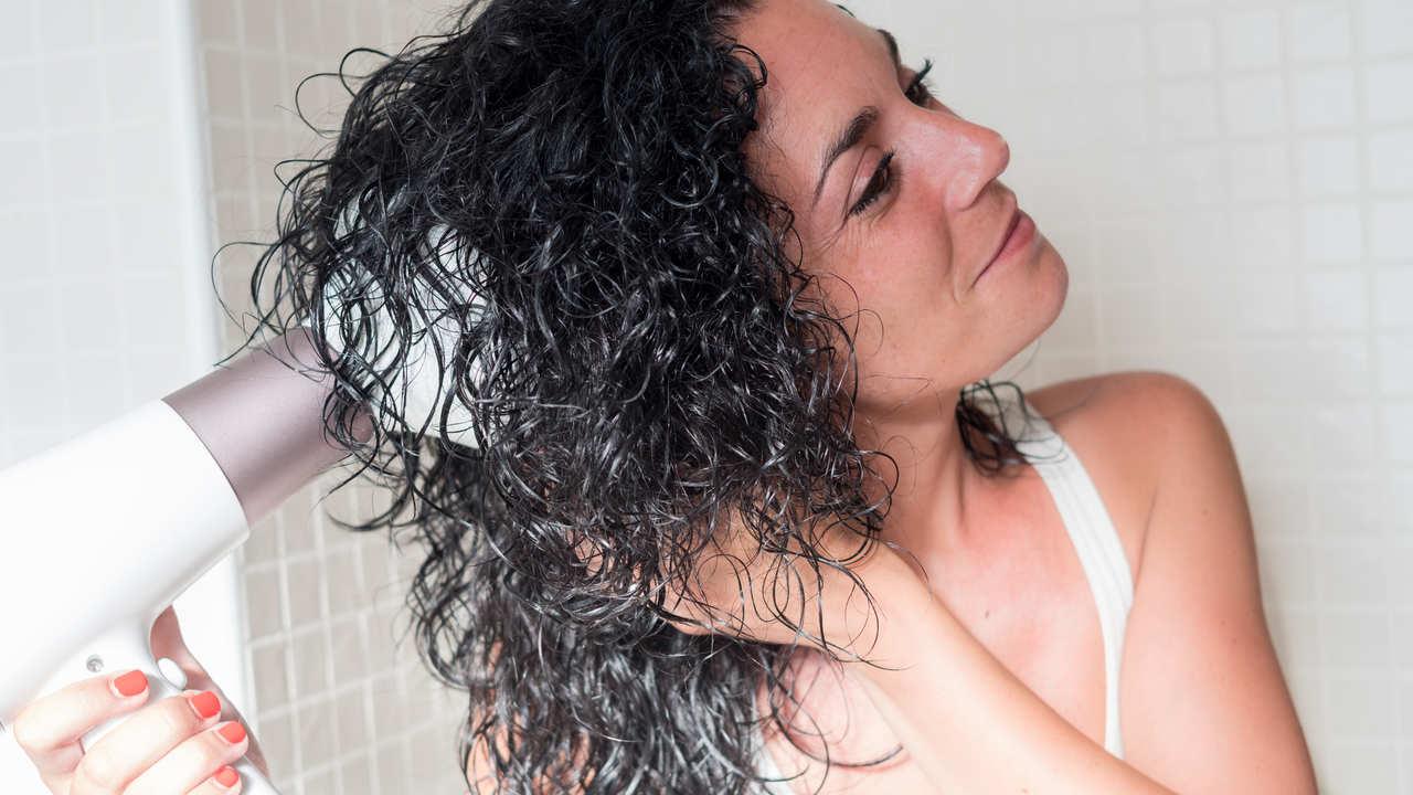 Mulher usando secador com difusor em banheiro