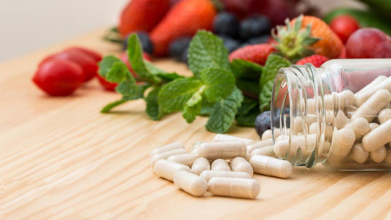 Vitaminas em cima de mesa de madeira ao lado de morangos