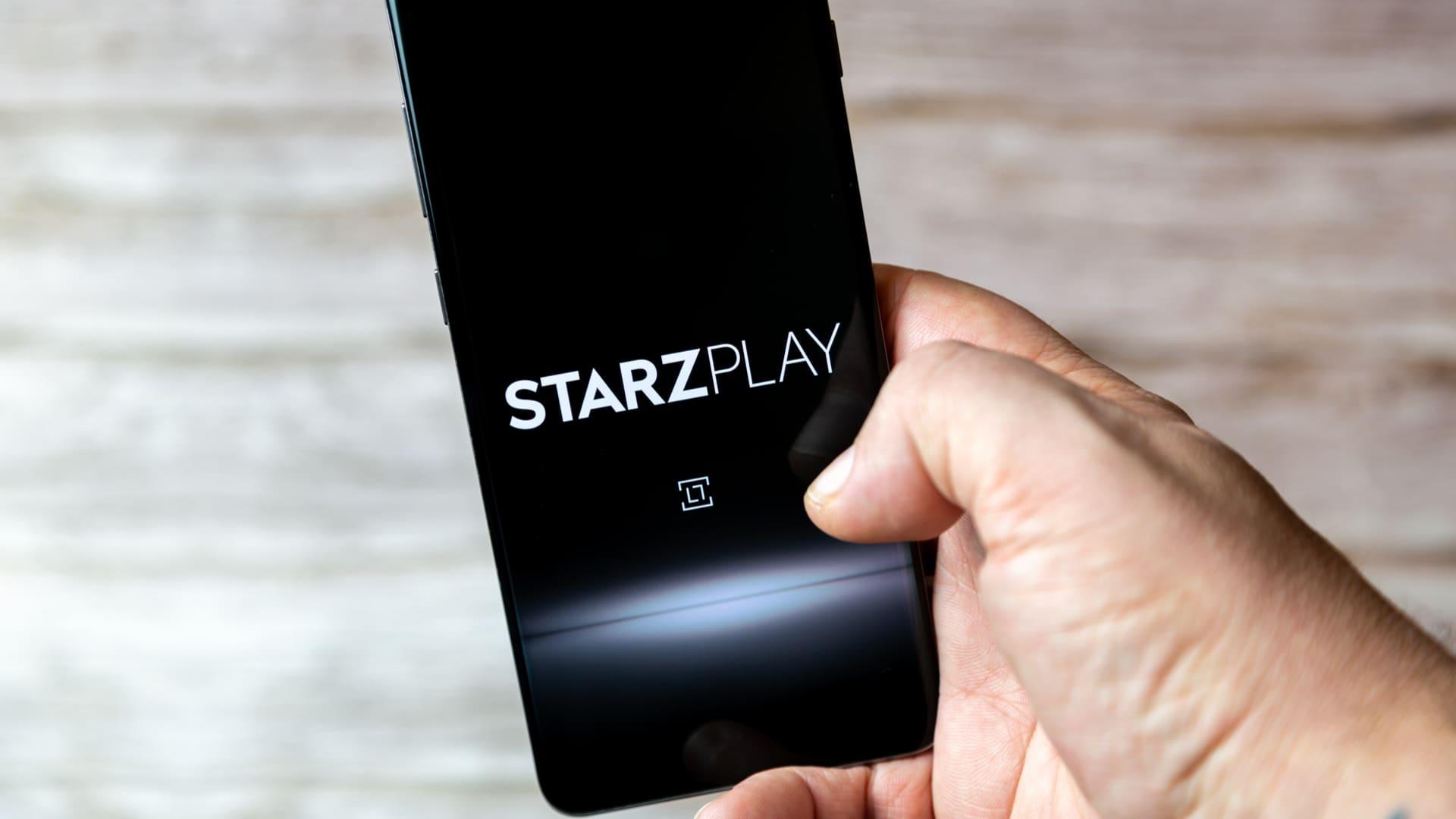 Celular com a logomarca do StarzPlay aberta em fundo preto, enquanto uma mão segura o dispositivo móvel.