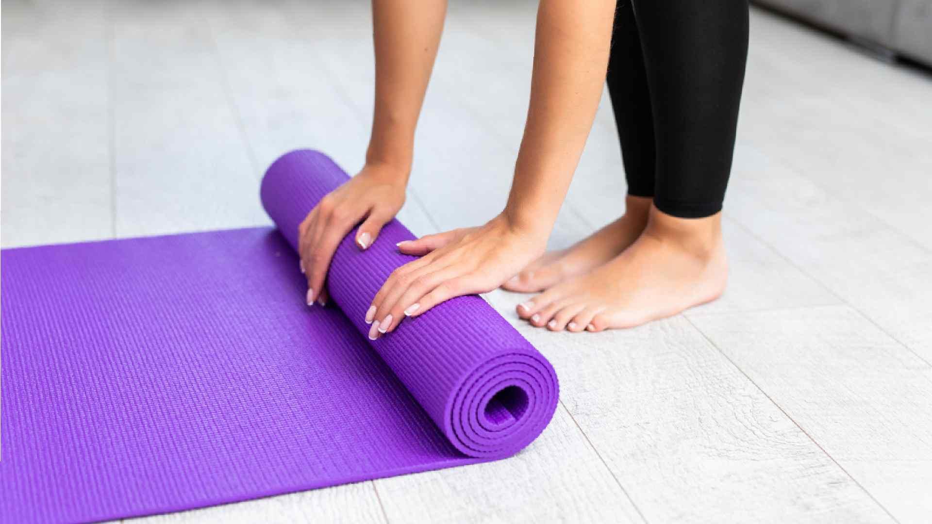 Mulher desenrolando um tapete de yoga roxo no chão