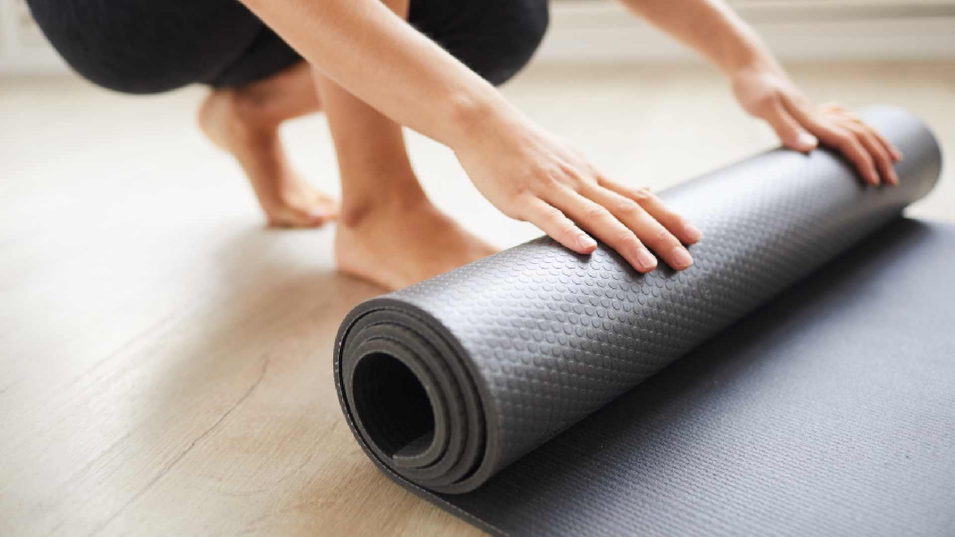 Mulher desenrolando tapete de yoga preto
