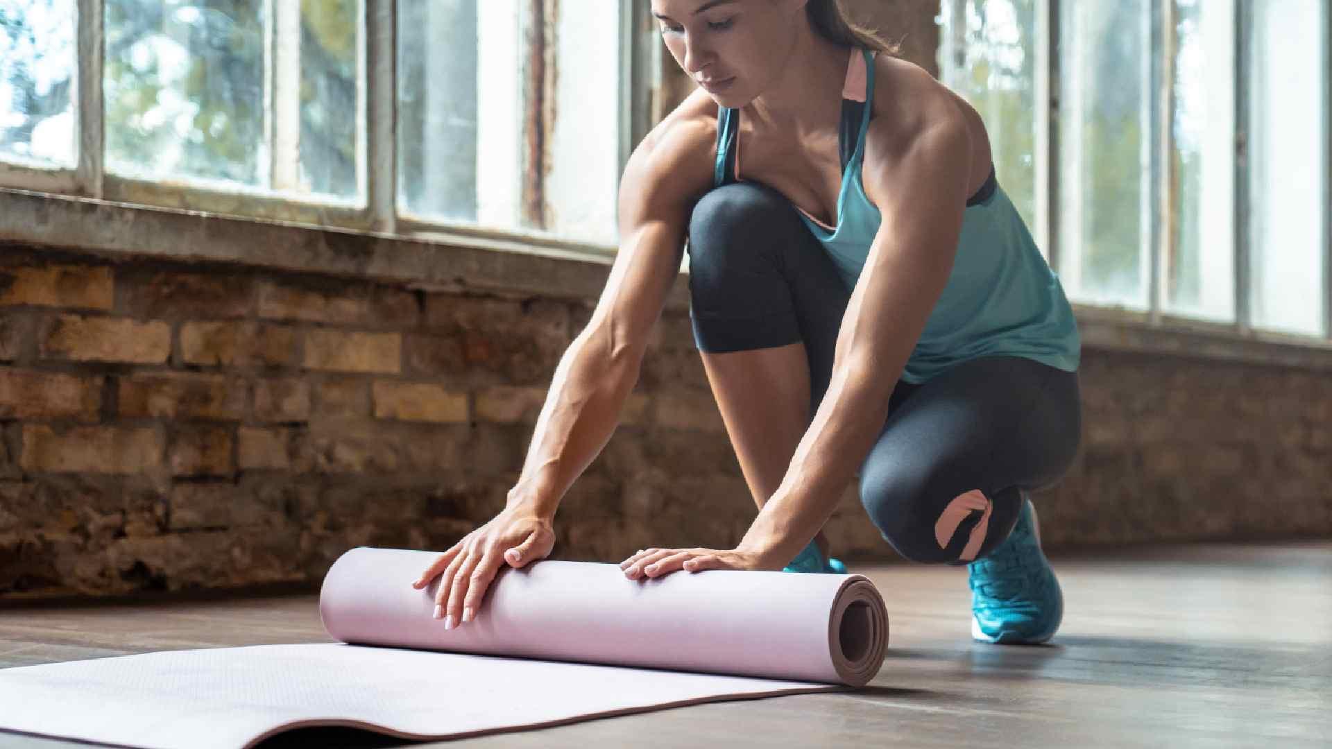Mulher enrolando o tapete de yoga rosa