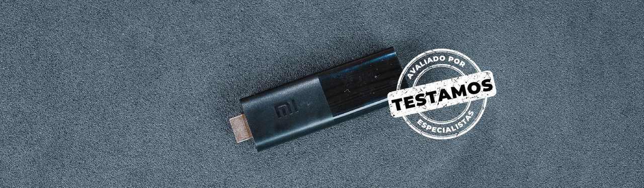 Mi TV Stick preto em um fundo cinza. Foto tem selo Testamos - Avaliado por especialistas.
