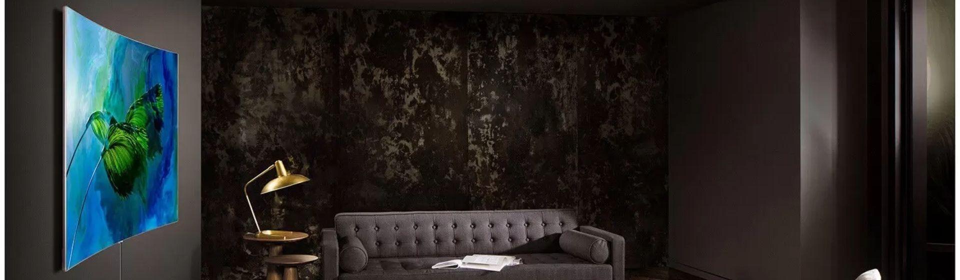Sala de estar elegante, em tons de cinza, na parede esquerda, a TV de tela curva Samsung Q8C