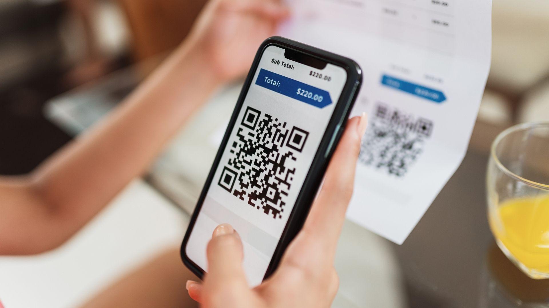 Mão segurando celular com tela do QR Code aberta
