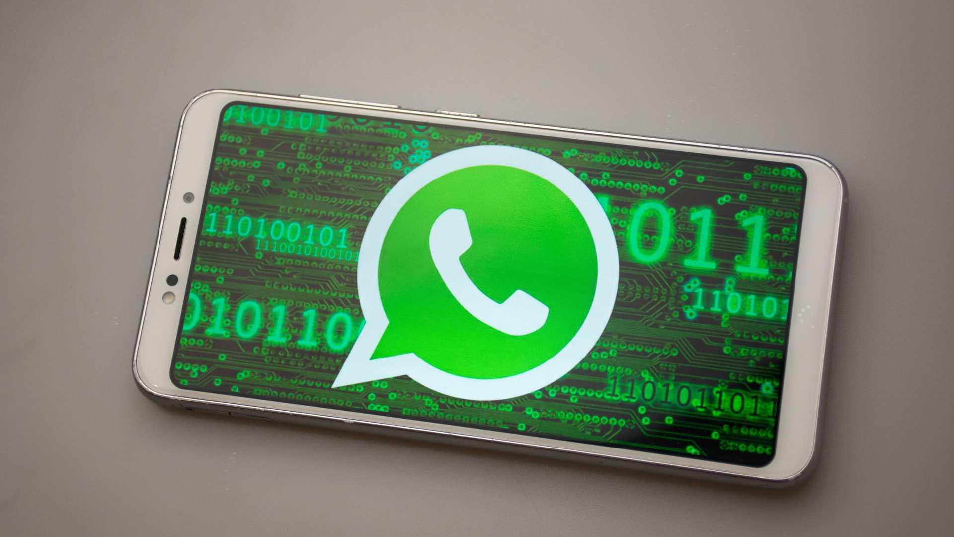 Celular com ícone do WhatsApp na tela, com códigos binários em verde ao fundo