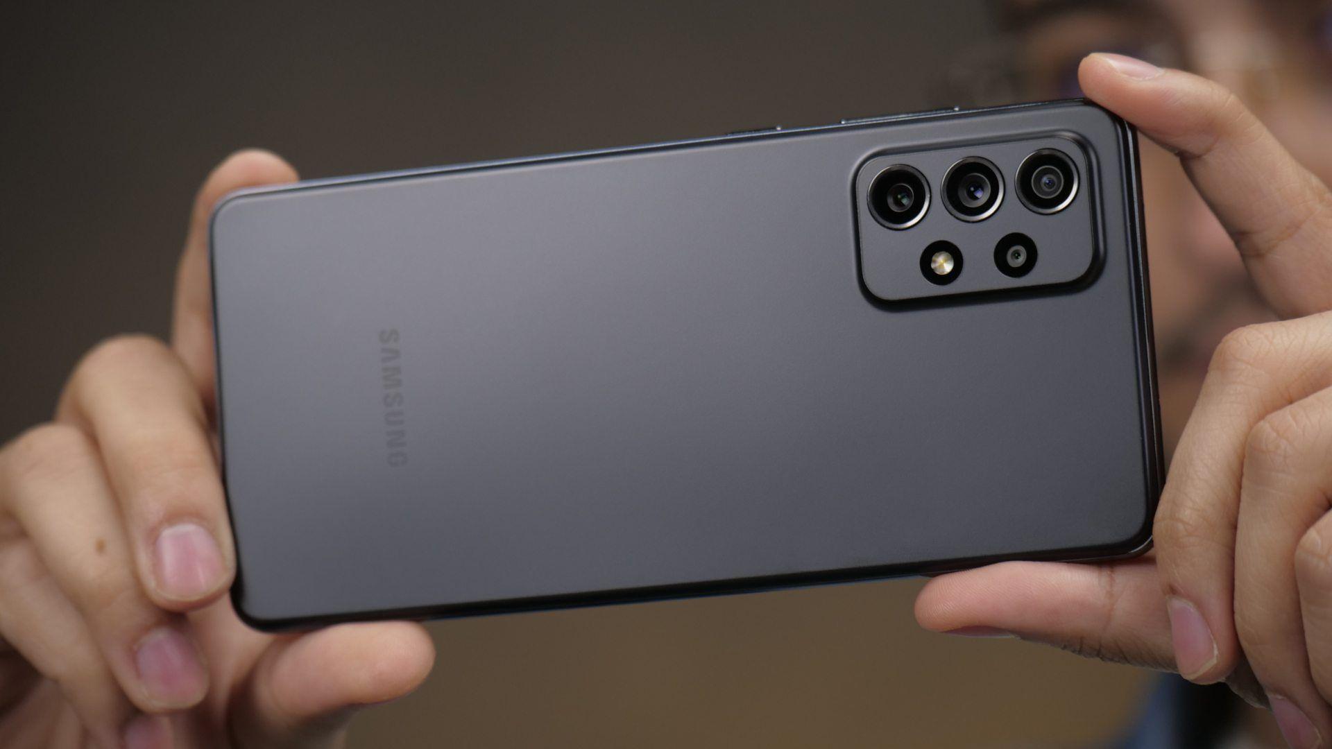 Homem segurando o celular Galaxy A72 preto na horizontal para tirar fotos