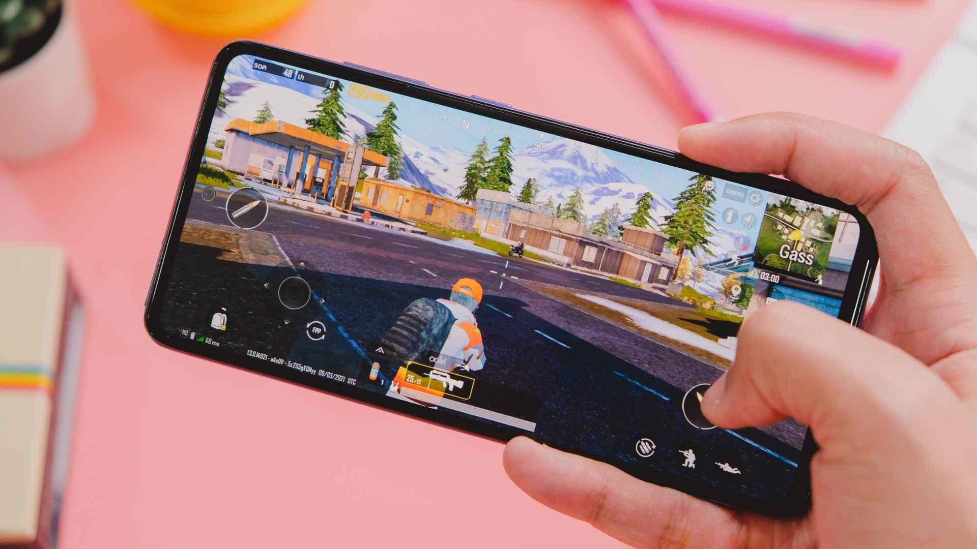 Foto de um celular A52 rodando um jogo e sendo segurado por uma mão