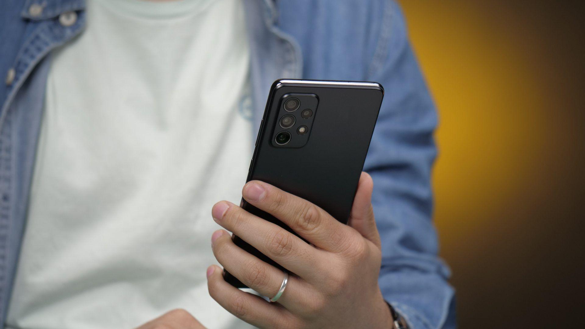 Celular Galaxy A72 na cor preta sendo segurado por uma mão