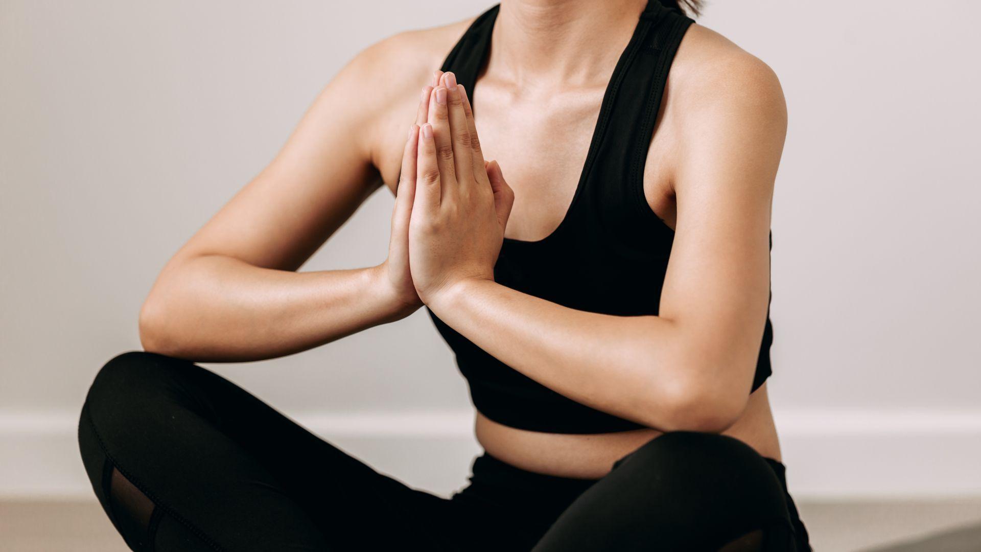 Mulher fazendo gesto de yoga