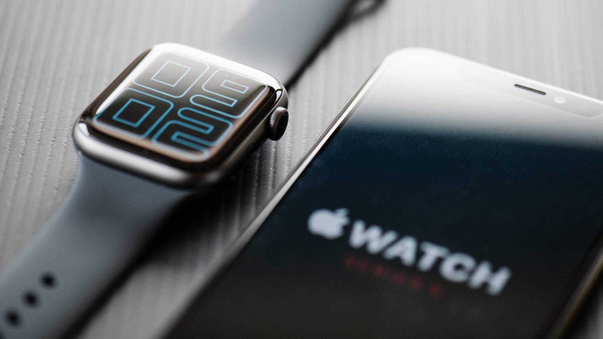 Apple Watch 5 ao lado de iPhone 11 em cima de mesa cinza