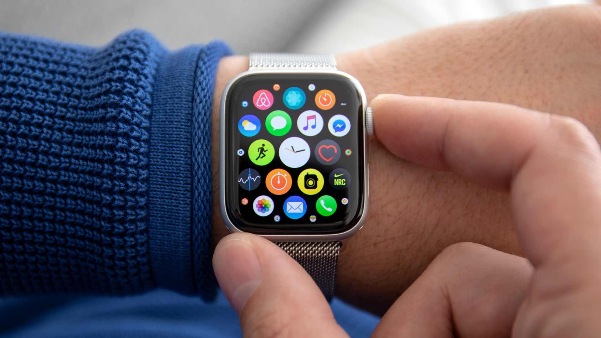 Apple Watch 5 com menu de aplicativos no pulso de homem com camisa azul