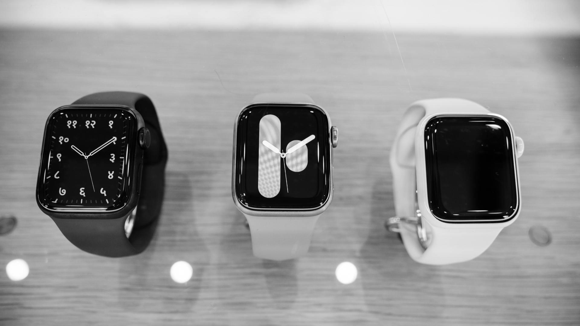 Três modelos diferentes de Apple Watch 5 sobre mesa de madeira